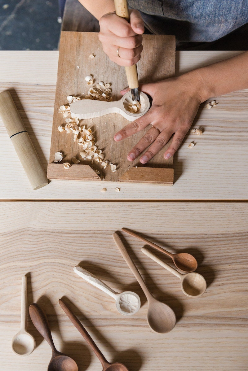 Melanie carves a wooden spoon by hand