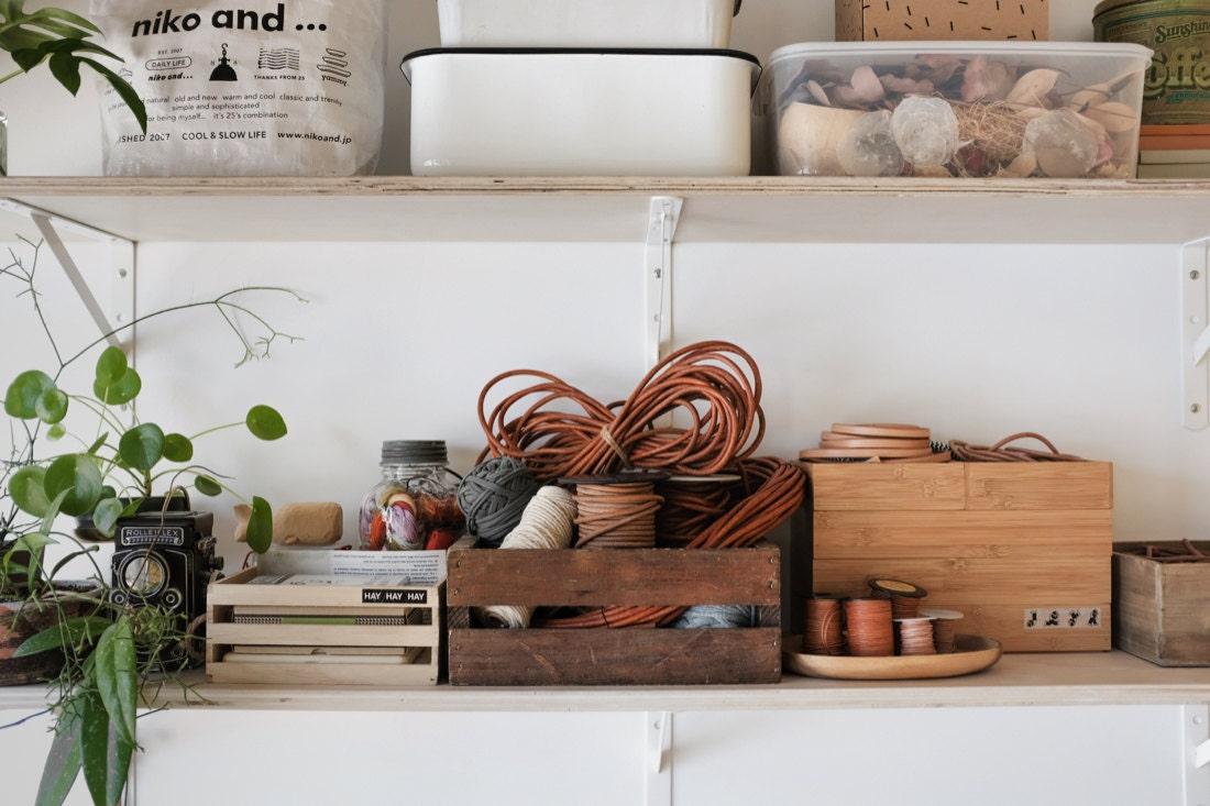 Thread, leather cord, and other supplies organized neatly on the shelves above Quynh's workstation