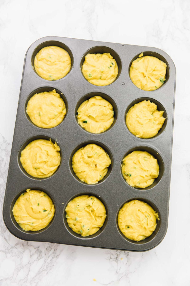 Spooning the mixture into muffin cups