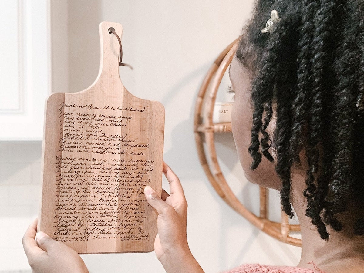 A woman holds up a wooden cutting board inscribed with a handwritten recipe.