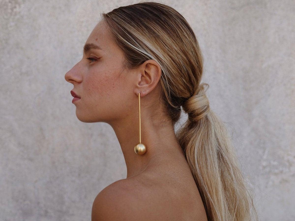 Spherical statement earrings on a model.