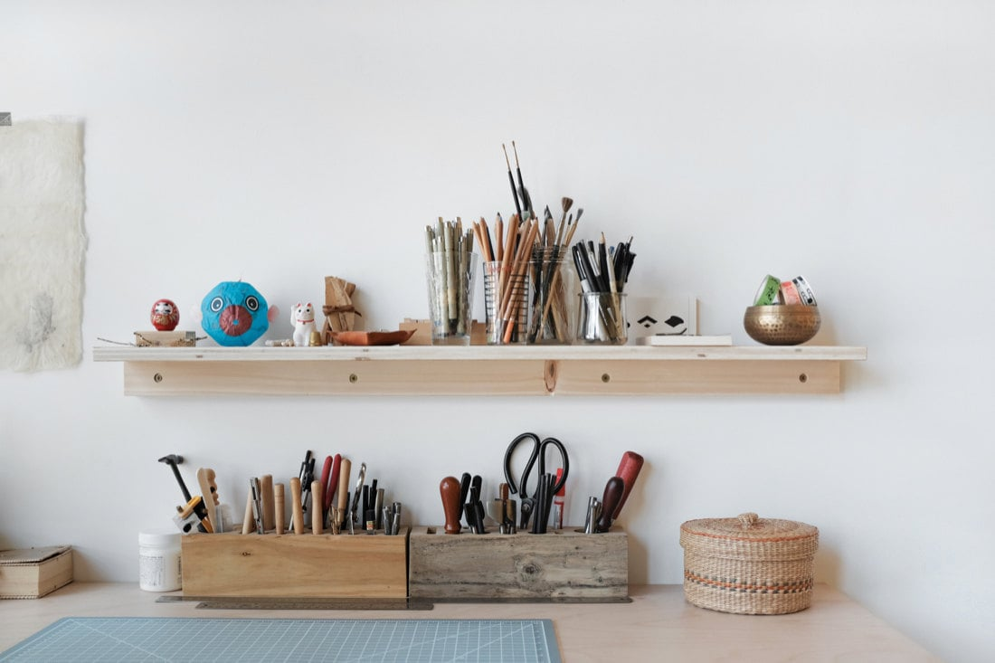 A closeup of Quynh's desk and shelf of tools and supplies
