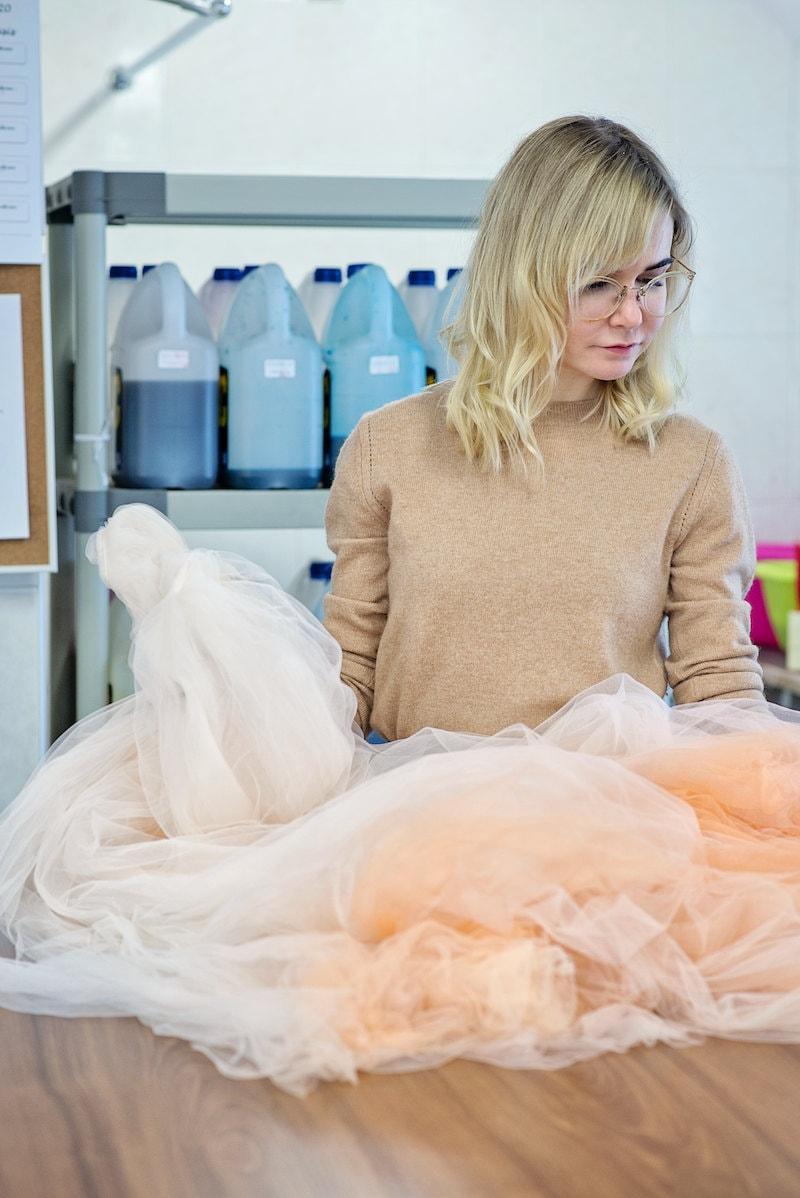 Inge examines a peach tulle skirt
