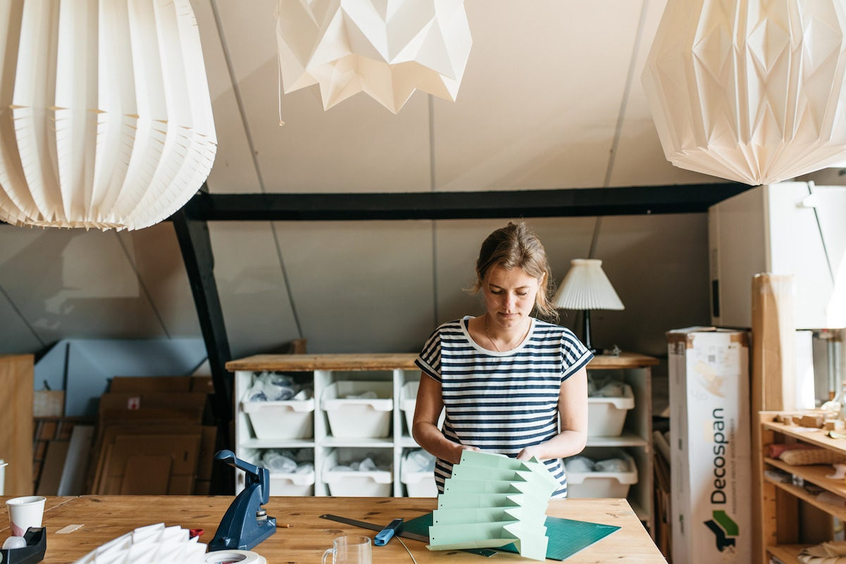 Nellianna folds a piece of mint green paper for a lamp