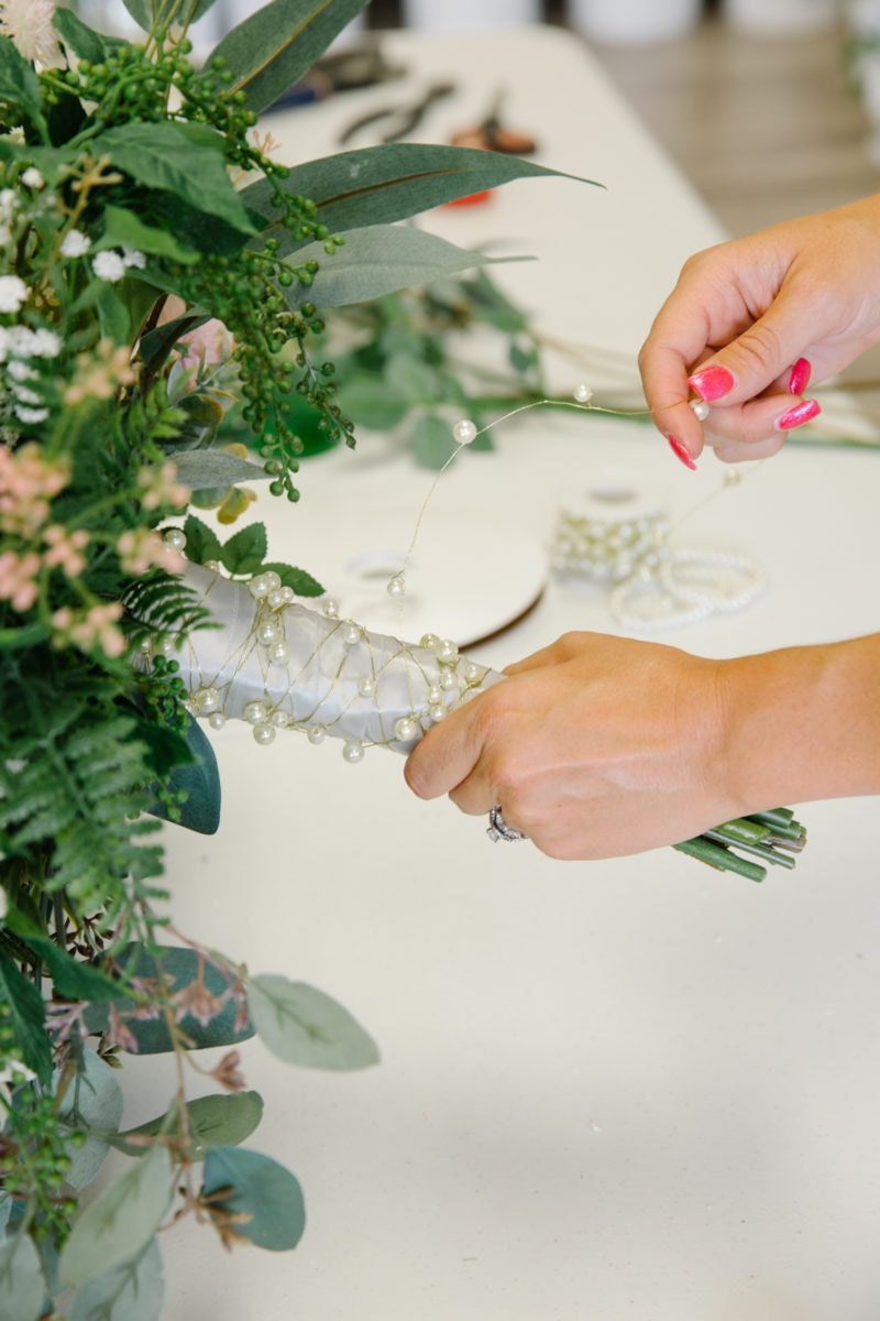 Brittany finishes a bouquet stem with decorative ribbons and pearls