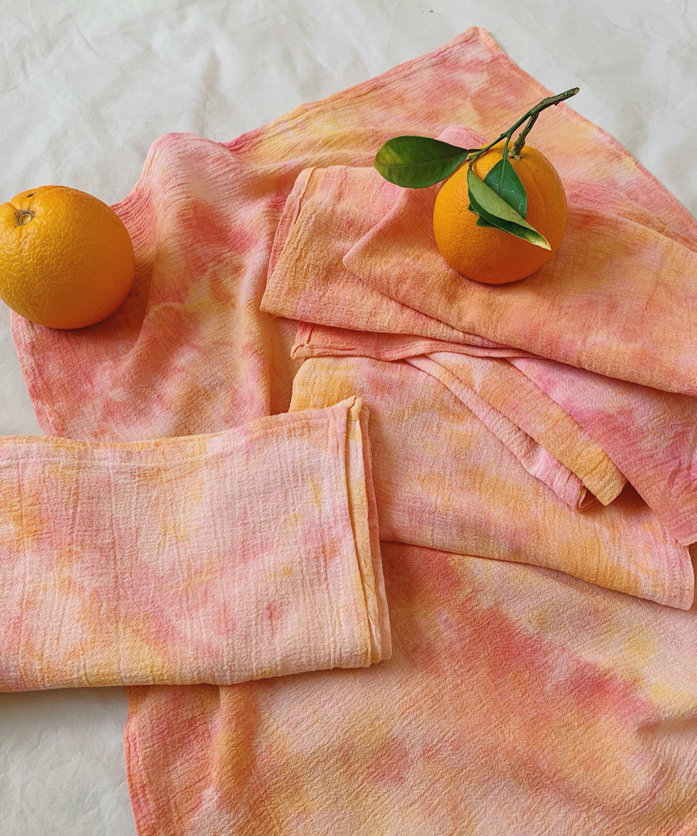 A set of peach-colored tie-dyed cotton napkins.