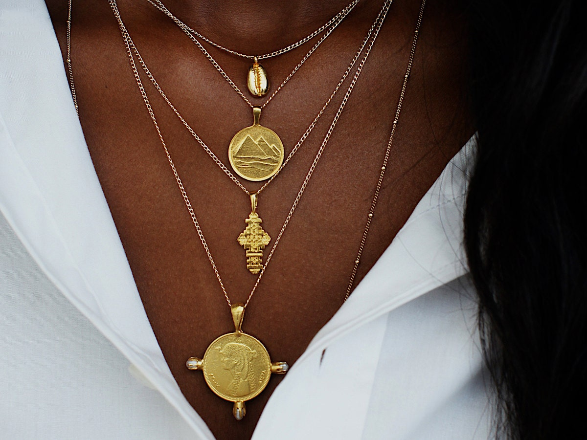 A woman models a stack of gold coin necklaces from Omi Woods