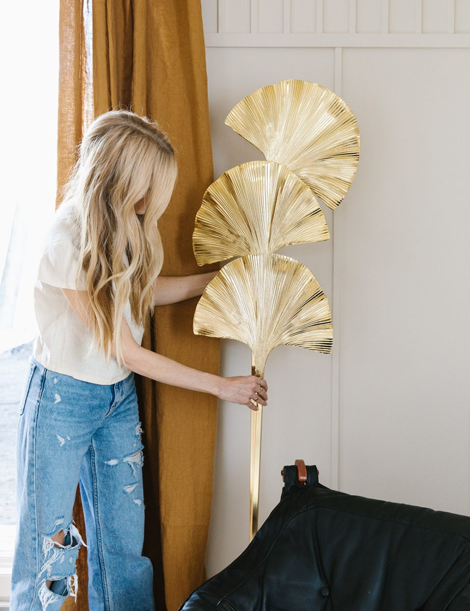Sarah moves a gold standing floor lamp that is taller than her and has three ginkgo-leaf shapes.