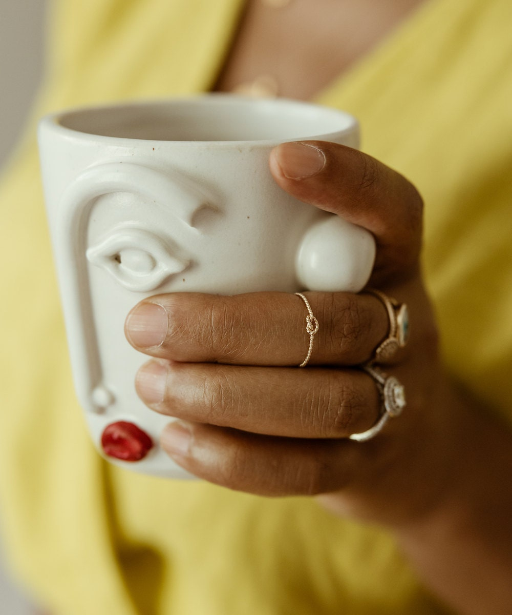 Shay wearing a gold rope knot ring and holding a face cup