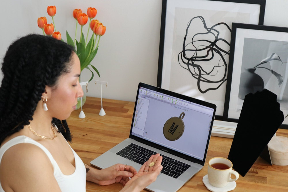 Sabrina mocks up a design for an initial pendant on her computer.