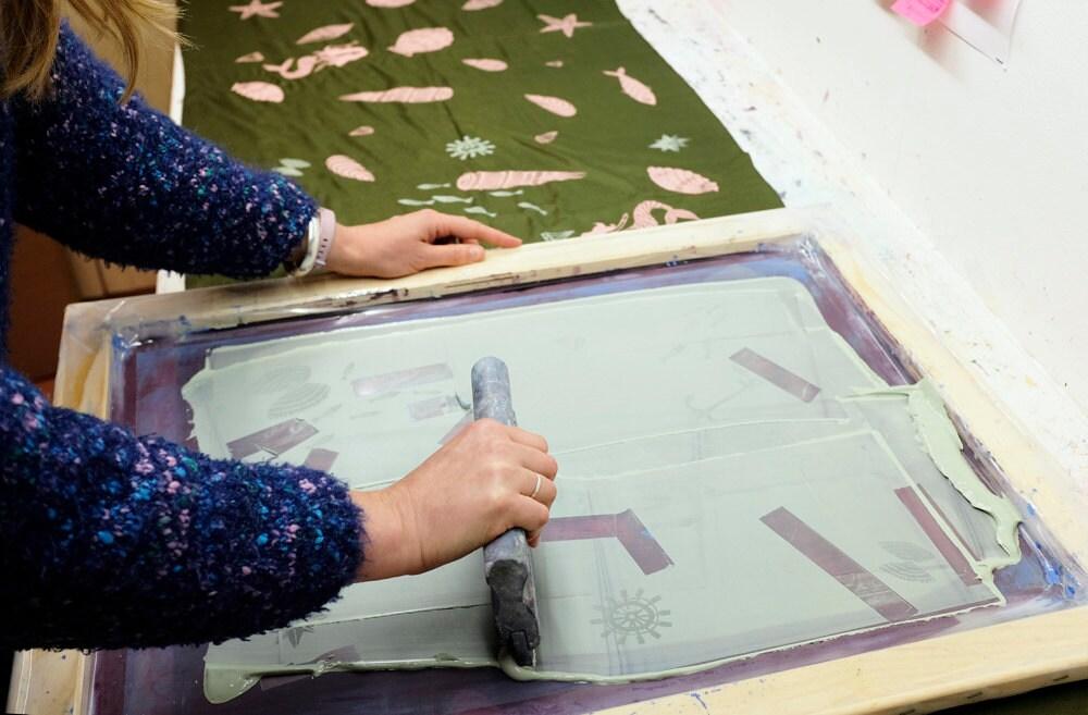 Lee screenprints a pattern onto a silk scarf.