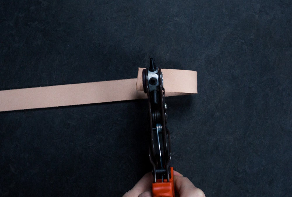 A leather hole punch perforates the strap