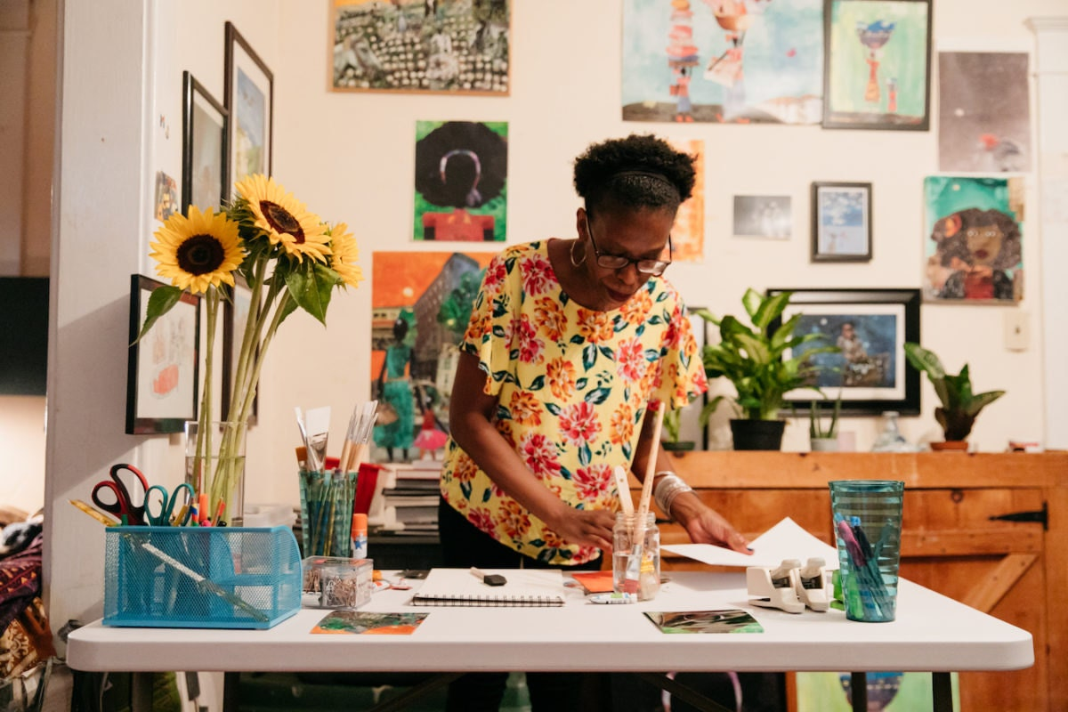 Mirlande works on a collage in her dining room studio