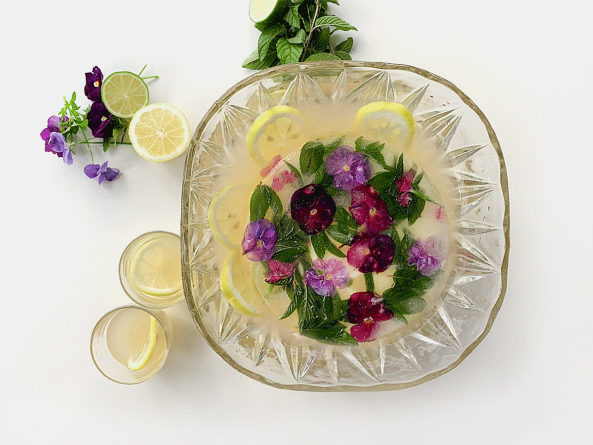 A bowl of summer punch with a decorative block of ice floating in the center.