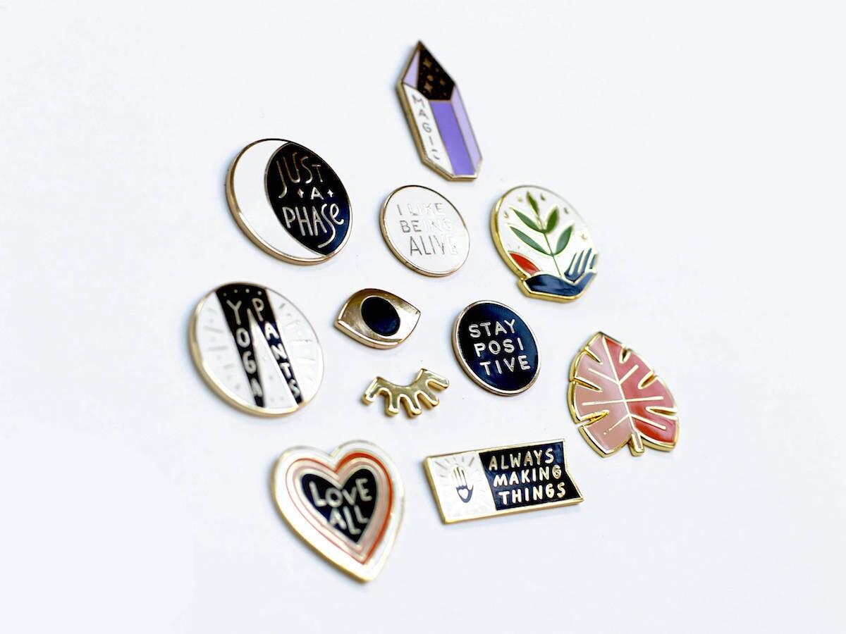 An assortment of motivational enamel pins