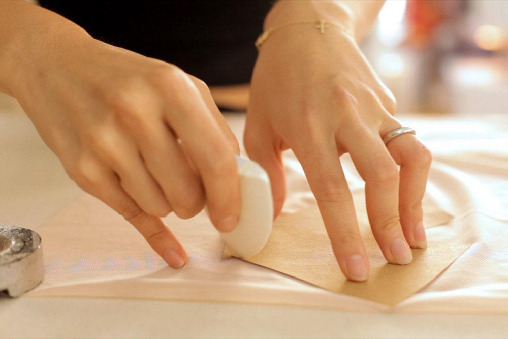 A closeup of Elma making a precise fabric cut