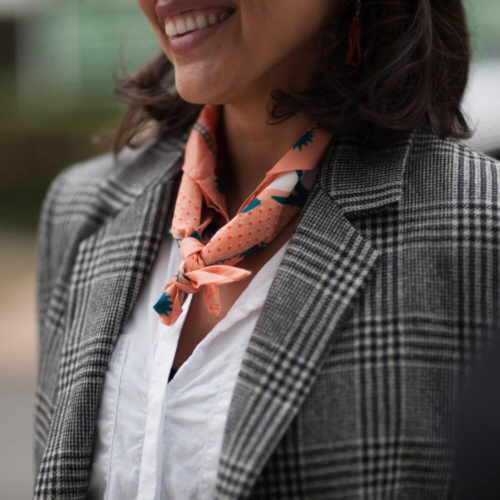 A woman models a bandana worn as a neckerchief from All Very Goods.
