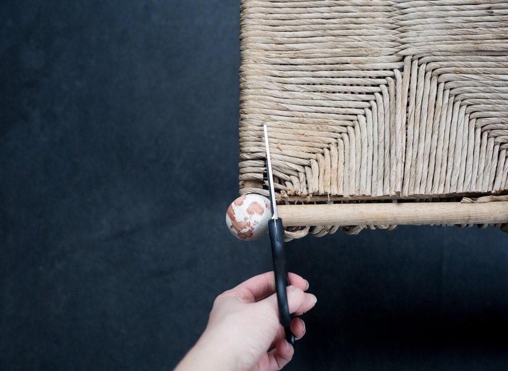Scissors cutting through woven seat of original stool