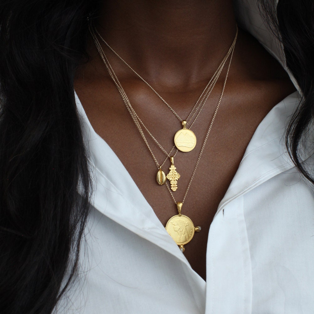 A woman models a stack of necklaces from Omi Woods, including her pyramid charm necklace, Ethiopian coptic cross, cowrie necklace, and Cleopatra coin necklace with pearls