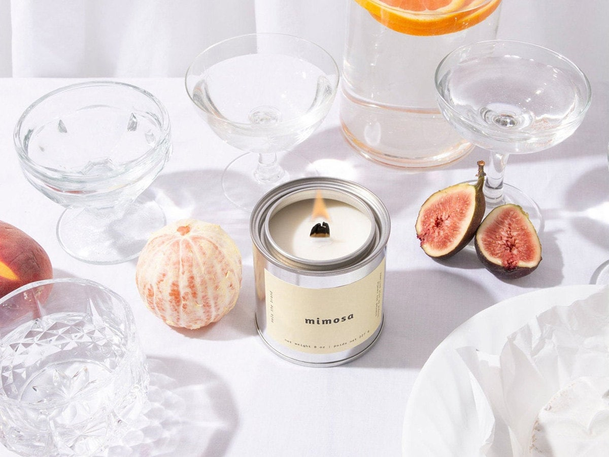A silver mimosa-scented candle surrounded by glassware and fruit.