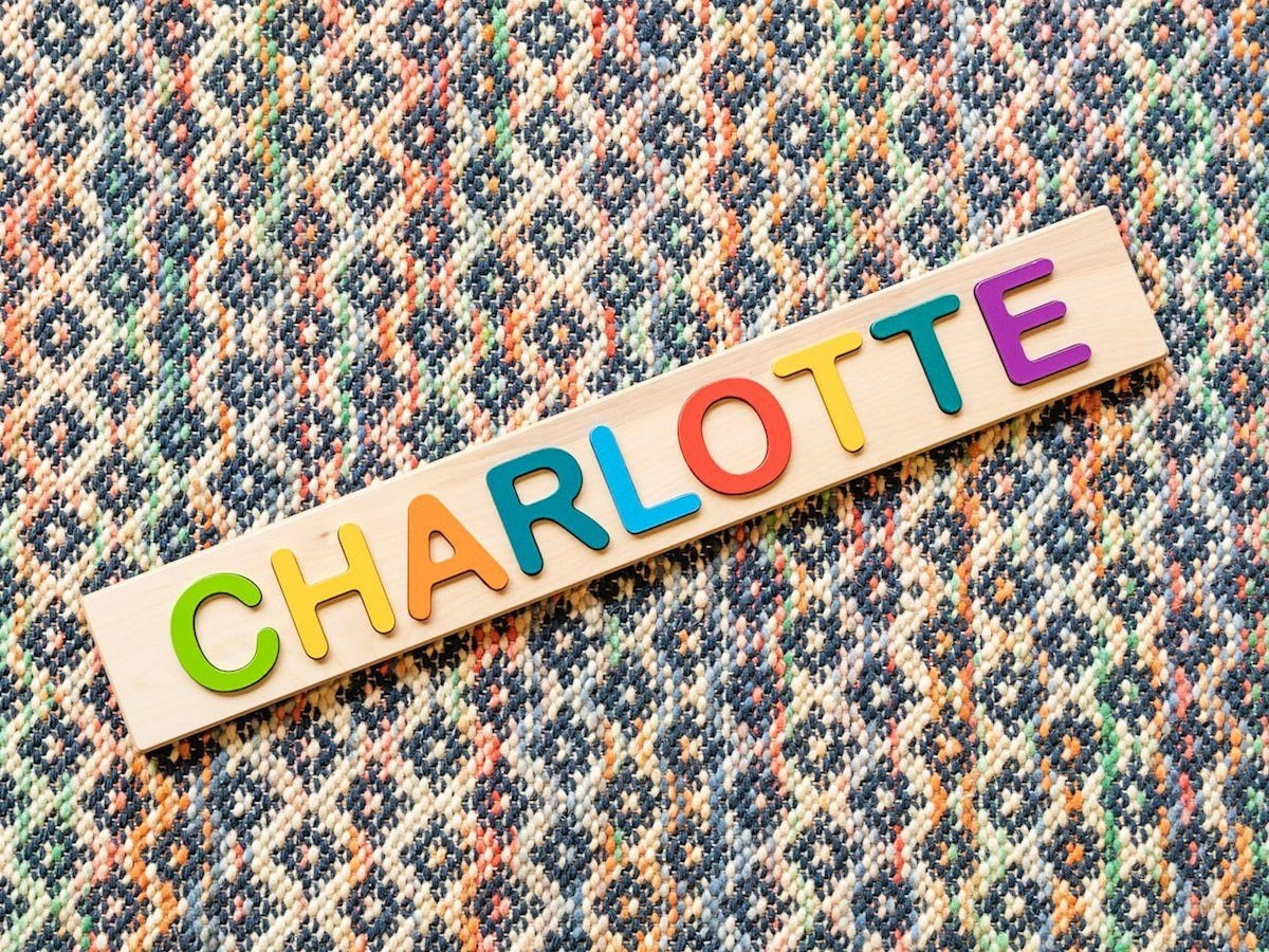 Product photo of a personalized children's name puzzle with wooden rainbow letters.