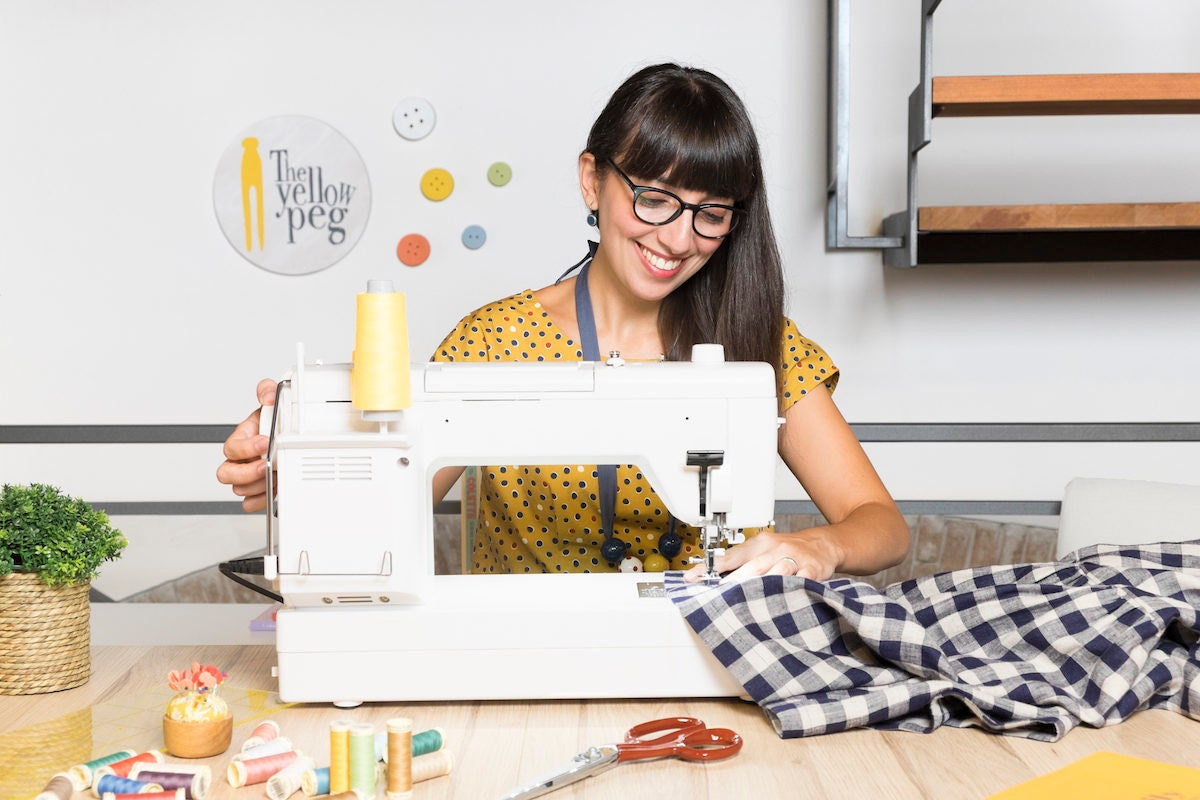 Simona sits at her sewing machine in her studio and works on an item in progress