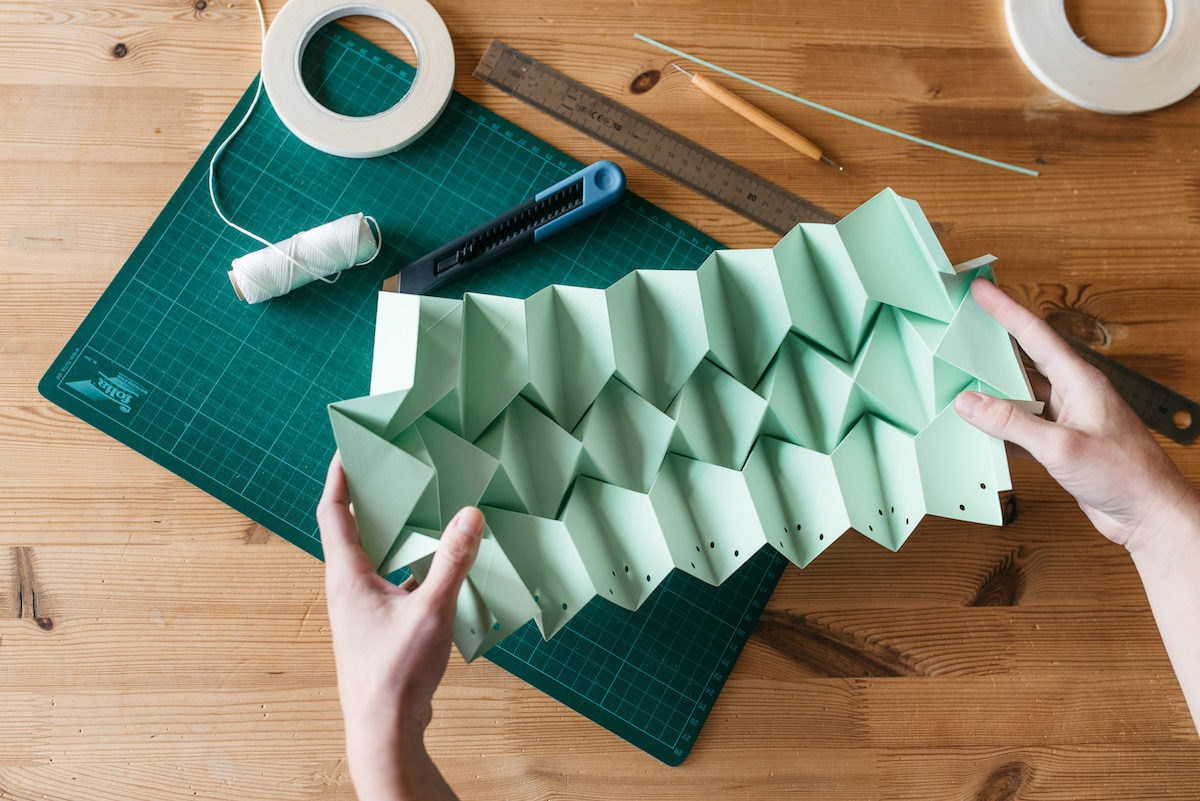 Close-up shot of the folded mint green paper lamp-in-progress