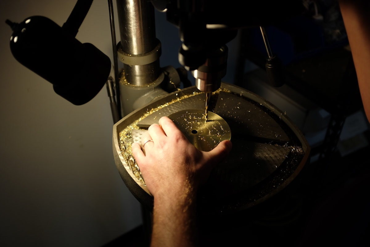 Kyle drills a hole in the brass base for a piece of lighting