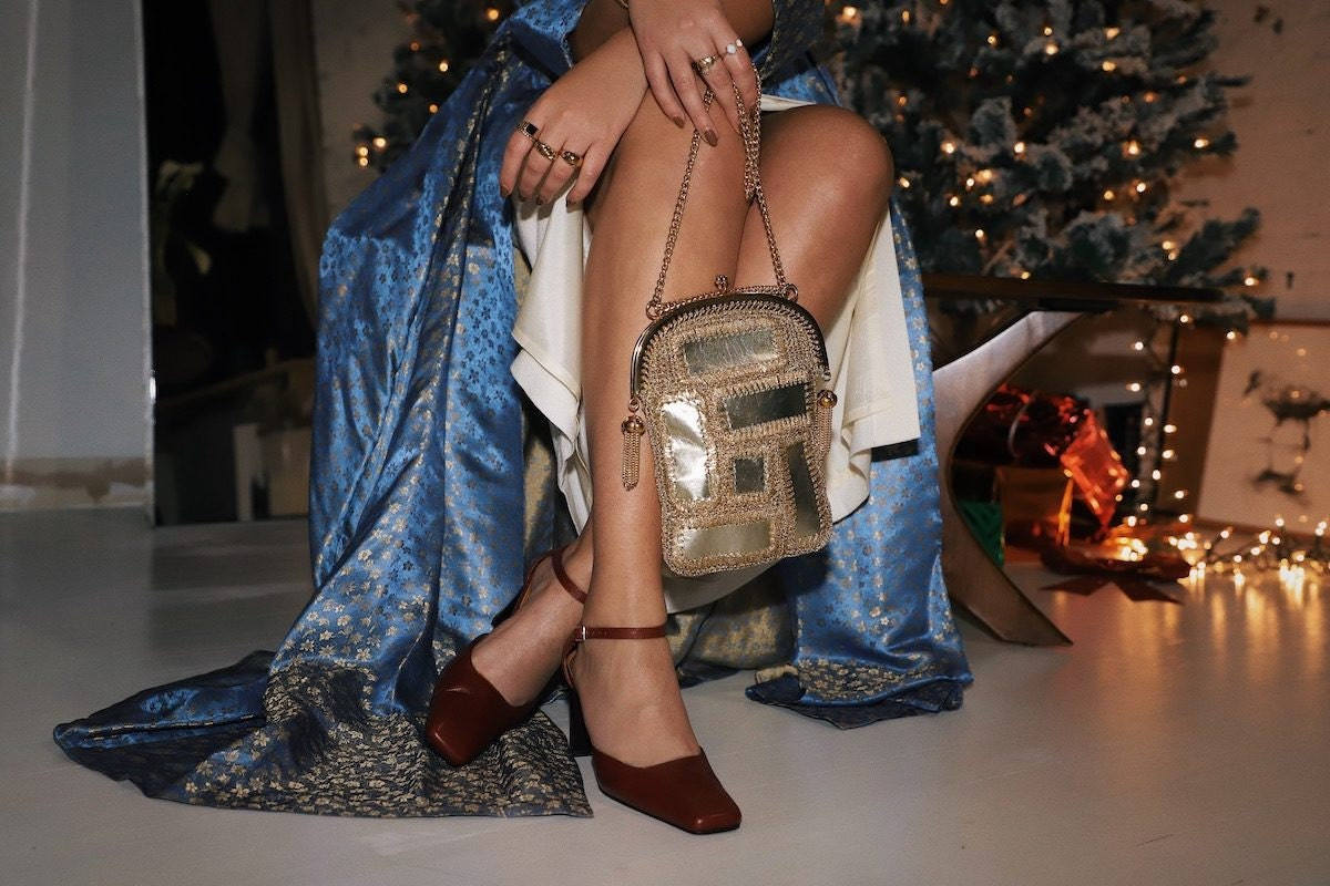 Close-up shot of Tara's vintage red shoes and vintage gold handbag from Etsy