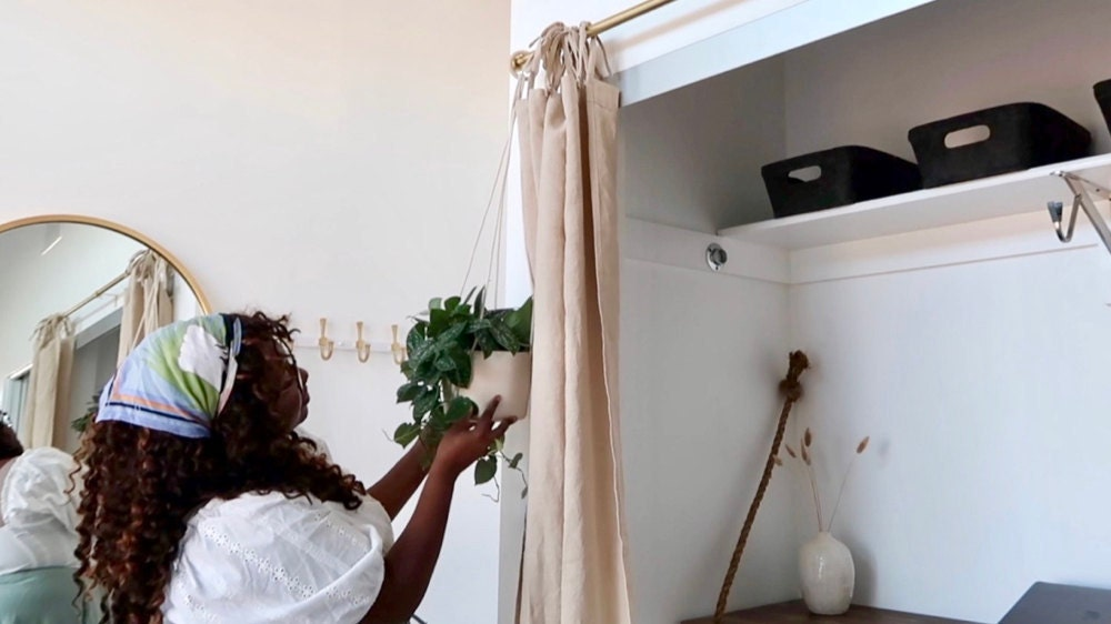 Janea accents her curtain wall with a hanging plant.
