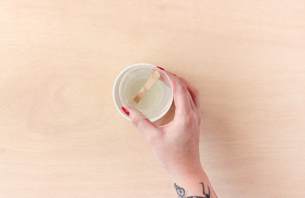 Rachel places her cup of mixed resin into a cup of hot water to allow air bubbles to rise to the surface.