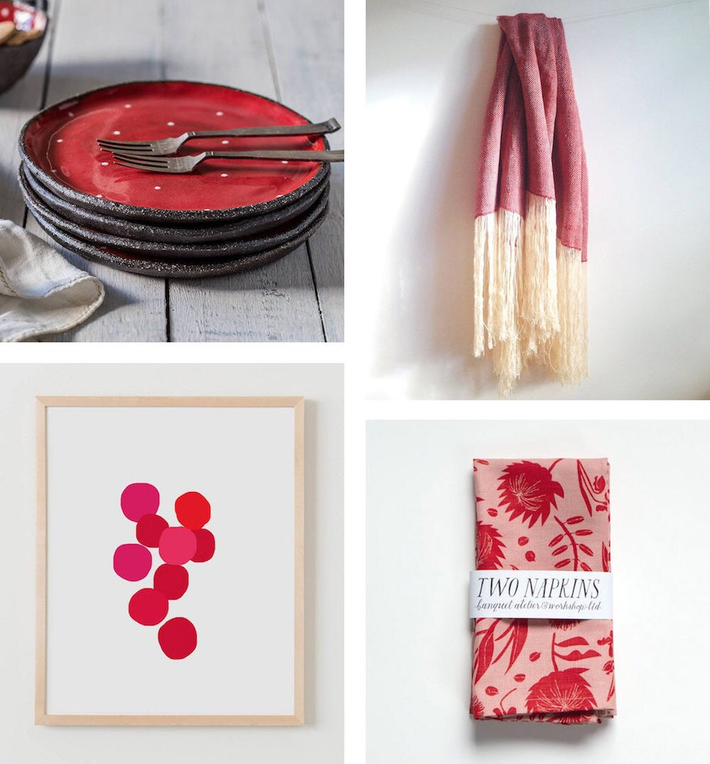 Four ruby-colored items for the home: ceramic dessert plates, a wool throw, a pair of linen napkins, and an abstract art print