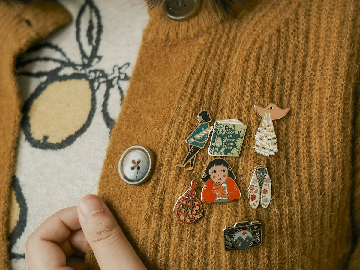 Enamel pins from Justine Gilbuena modeled on a sweater