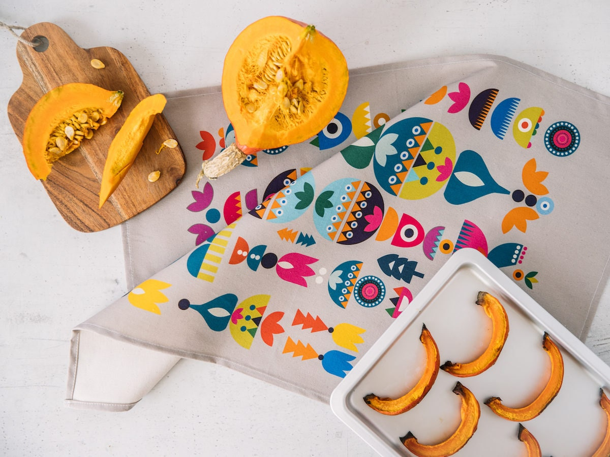 A colorful screen-printed tea towel featuring a Scandinavian-style illustrated pattern, from Softer and Wild.