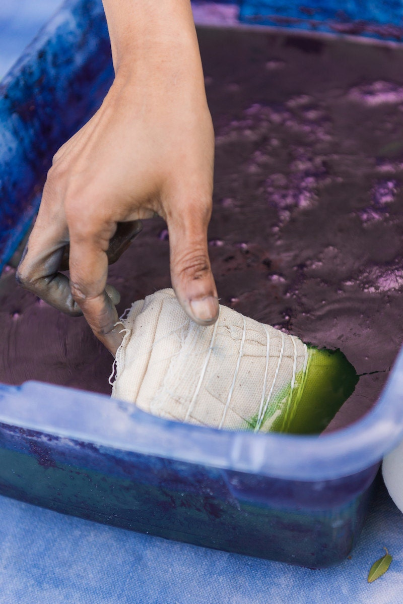 Rajni places a bundle of bound fabric into a vat of dye