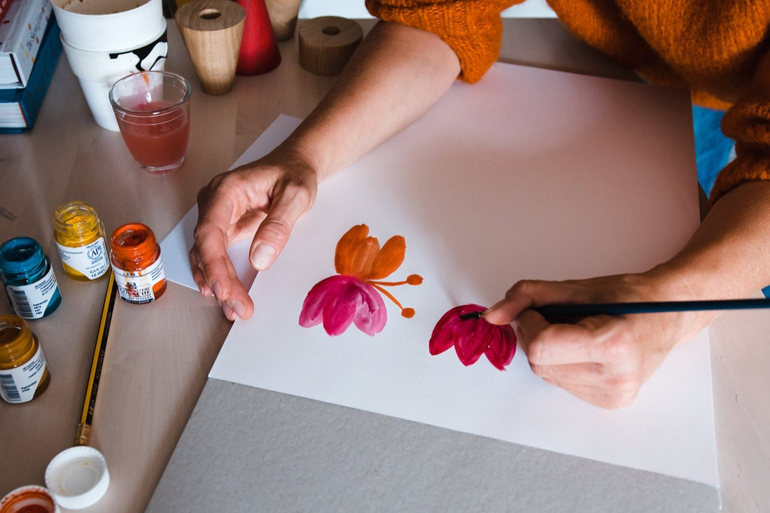 Tatiana paints colorful shapes on paper.