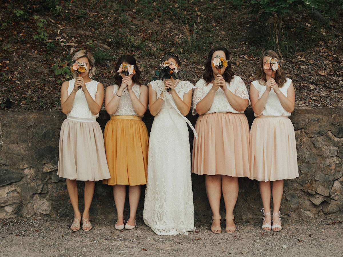 Bridesmaids and bride pose holding bouquets in front of their faces