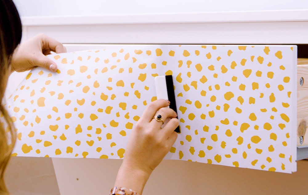 A woman smooths out air bubbles with a smoothing tool as she applies peel-and-stick paper to a dresser drawer