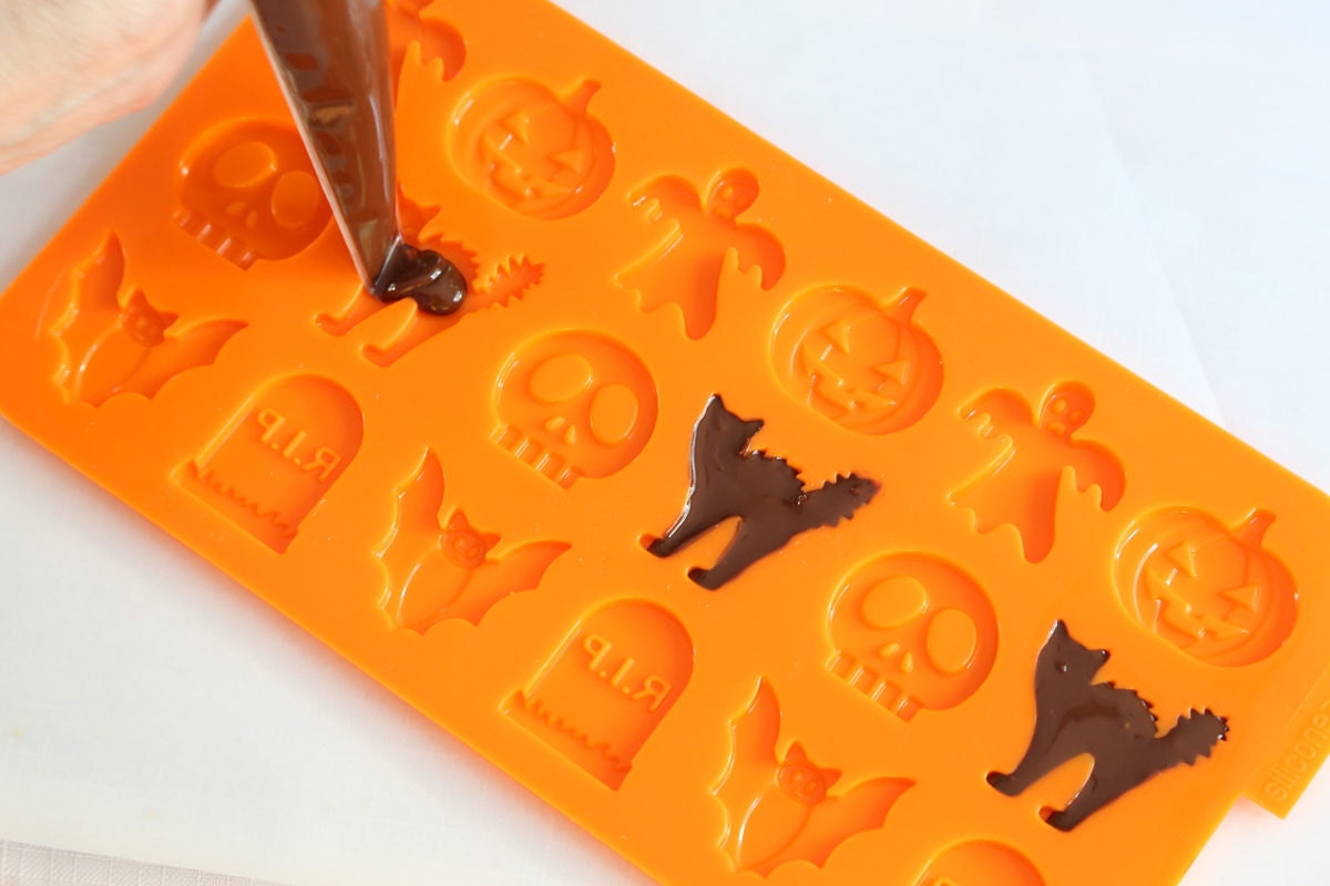 Filling a silicone candy mold with melted chocolate to create candy cats.