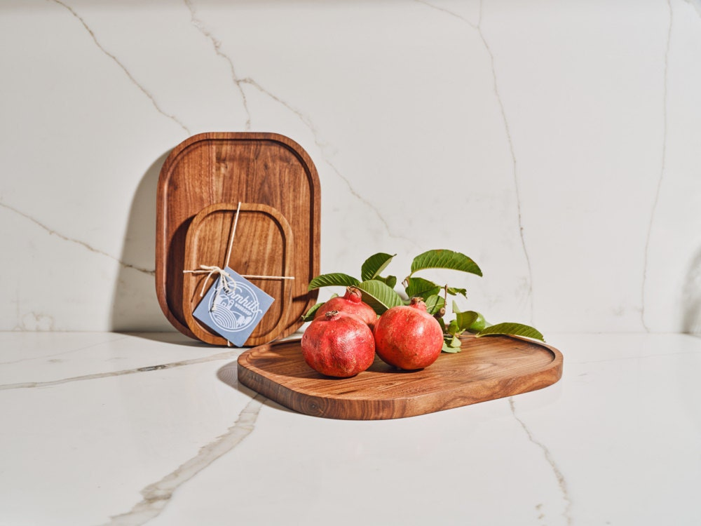 A styled shot of walnut serving trays from the Tan France x Etsy collection