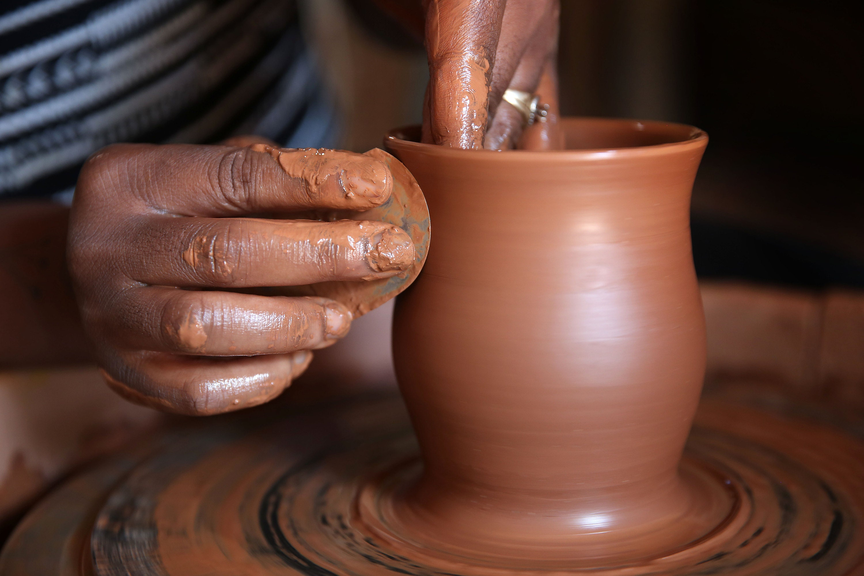 Hands spinning clay to make a vase