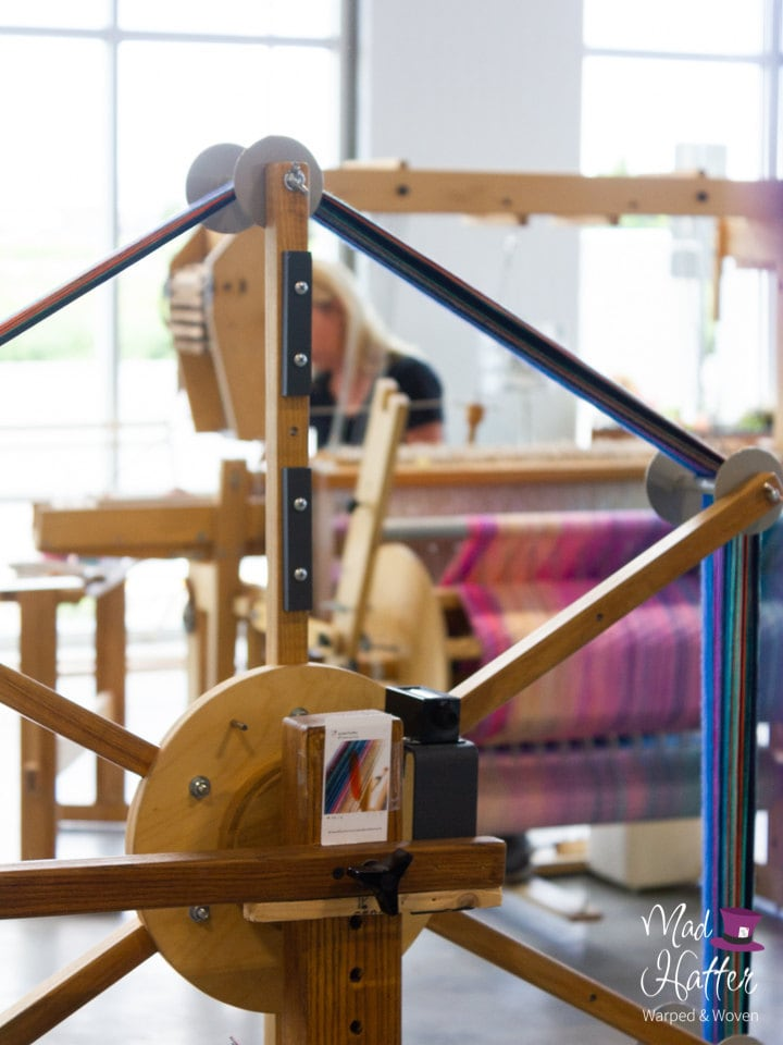A wooden warping wheel inside of Mad Hatter Warped & Woven Studio. Wheel has blues, purples, greens, and other colours of thread on it. In the back, Wildflower is blurry and is weaving on a wooden loom with threads of pinks, creams, and blues. There are large windows with sunlight coming through in the background.