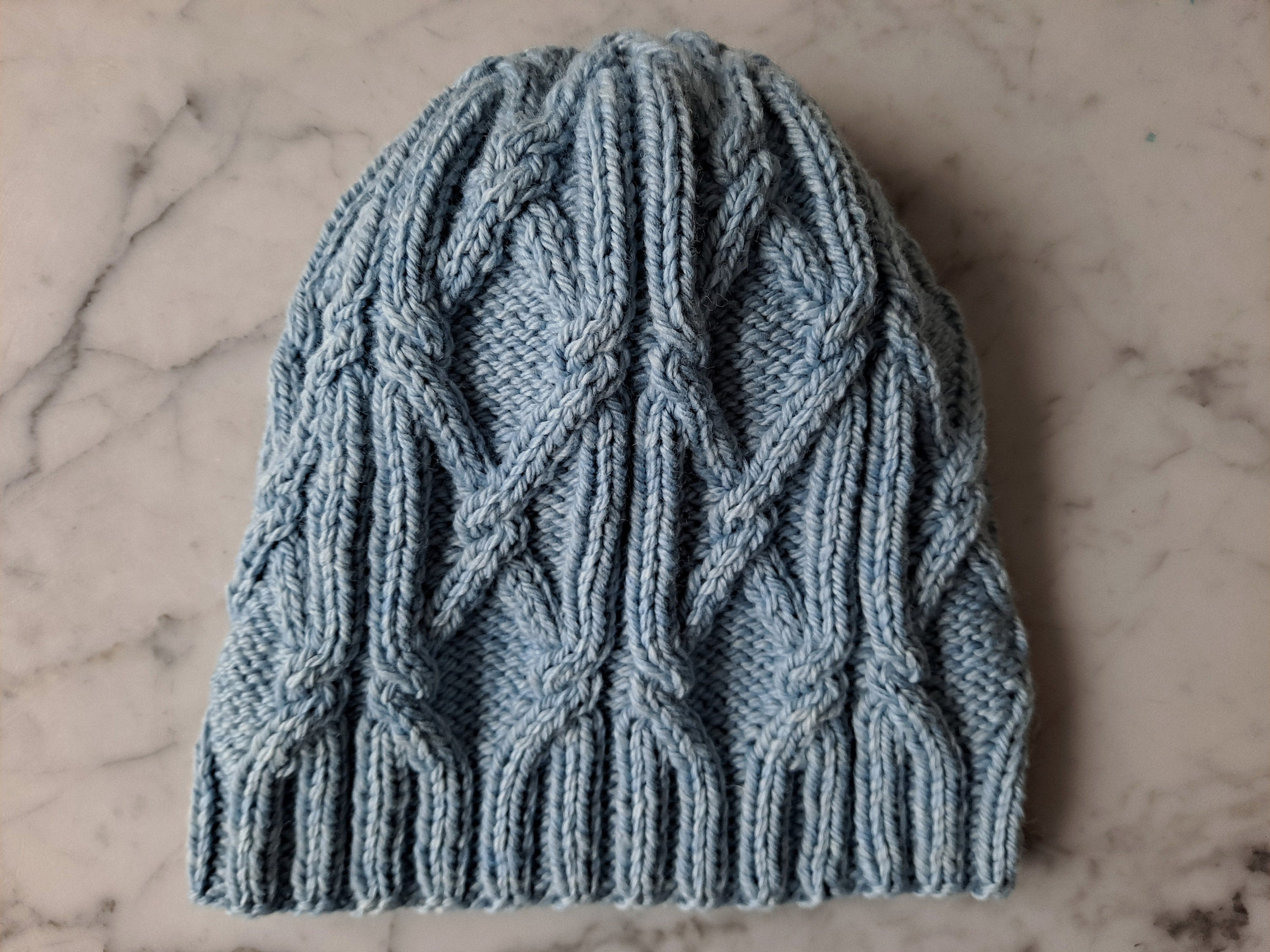 A pale blue cabled hat lies flat on a marble background.