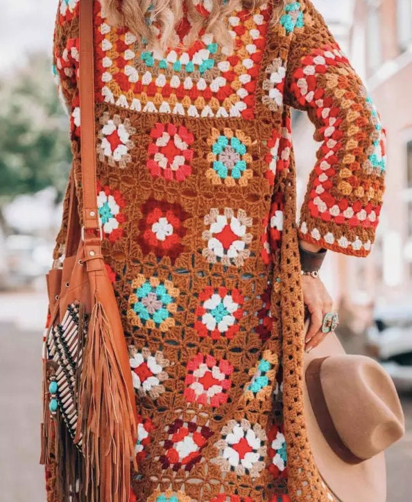 Woman wearing a Crochet Granny Square Coat and holding a hat with a bag over her shouder