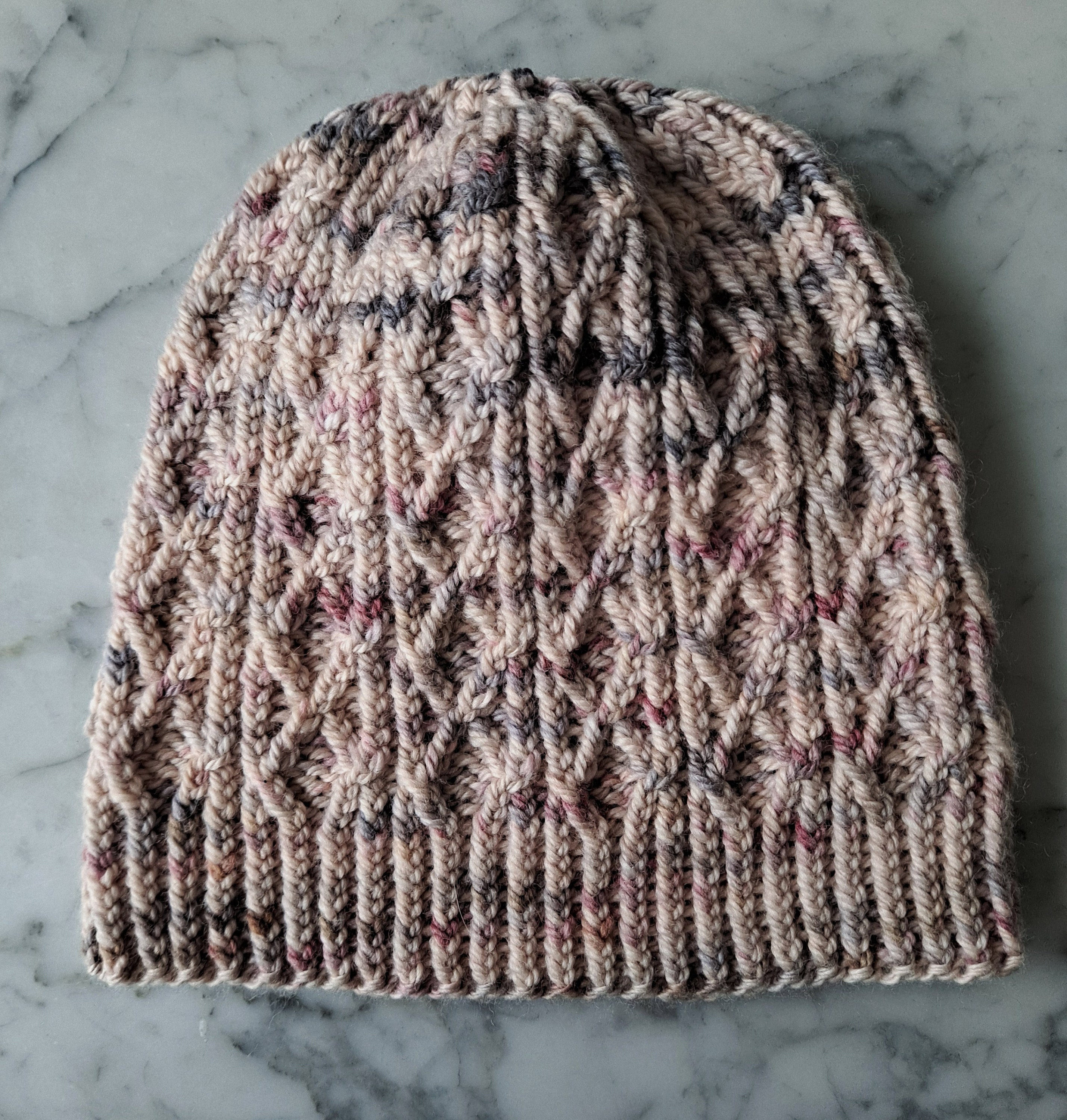 A pale pink cabled knitted hat lies flat on a marble background.