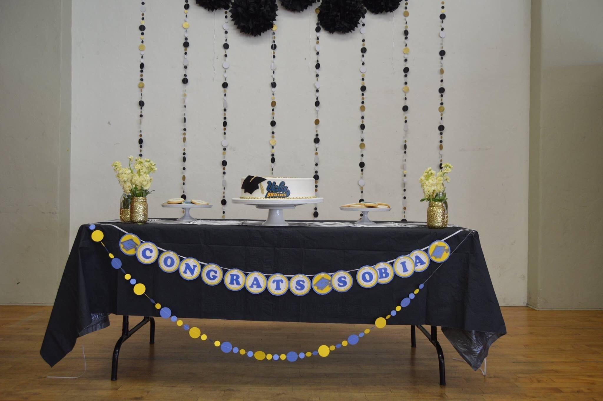 Congratulations banner with UCLA decor and gold and black glitter garlands