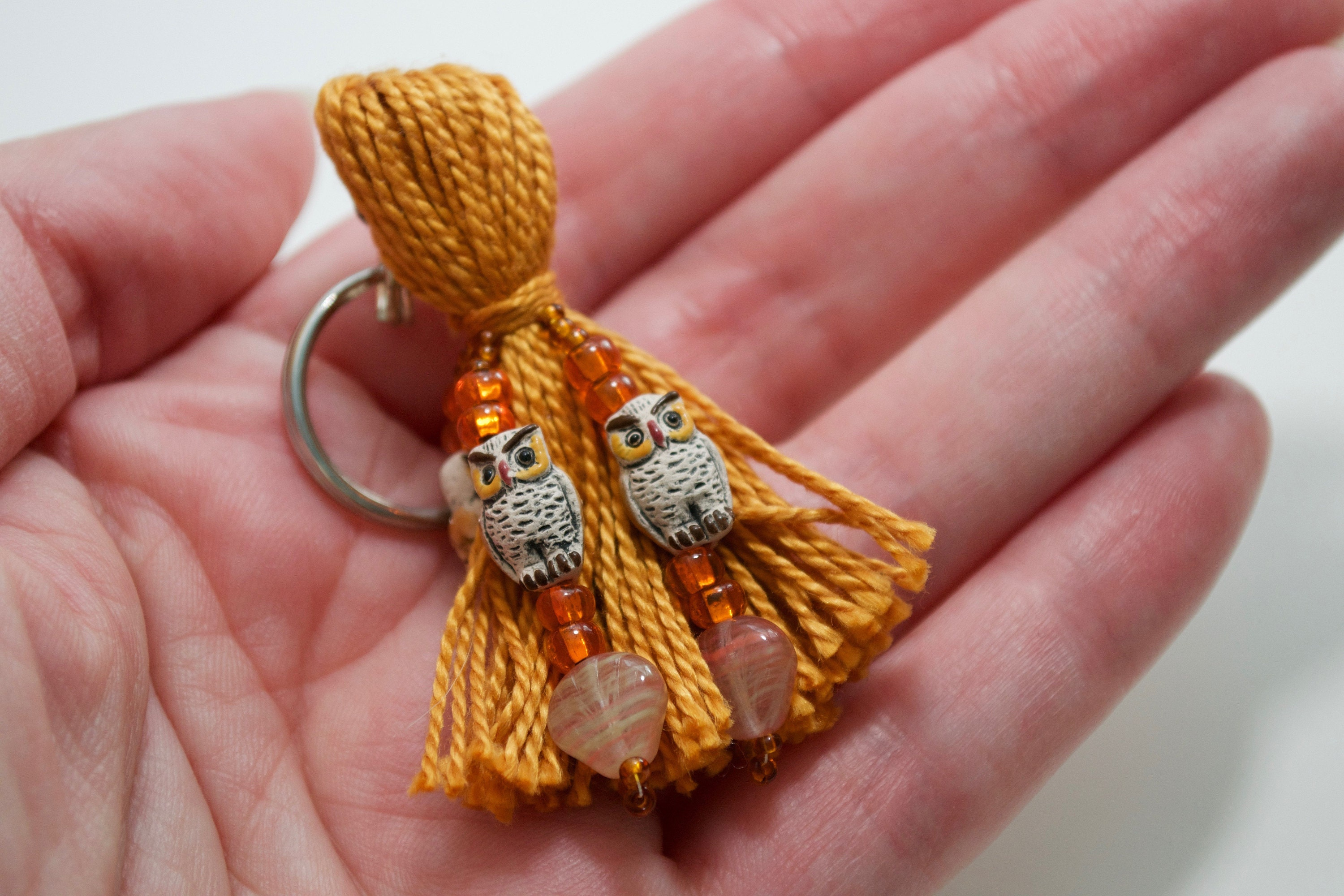 Brown owl beaded tassel keyring, held in hand