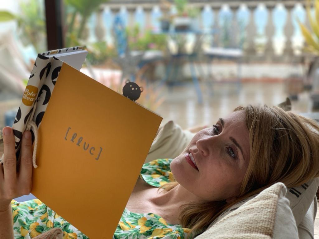 Otra foto de Núria Casals tumbada, mirando su álbum de b-paper.