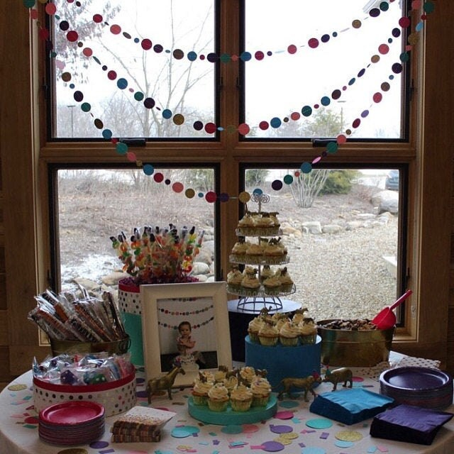 cake and food table for party with circle garlands hanging in window