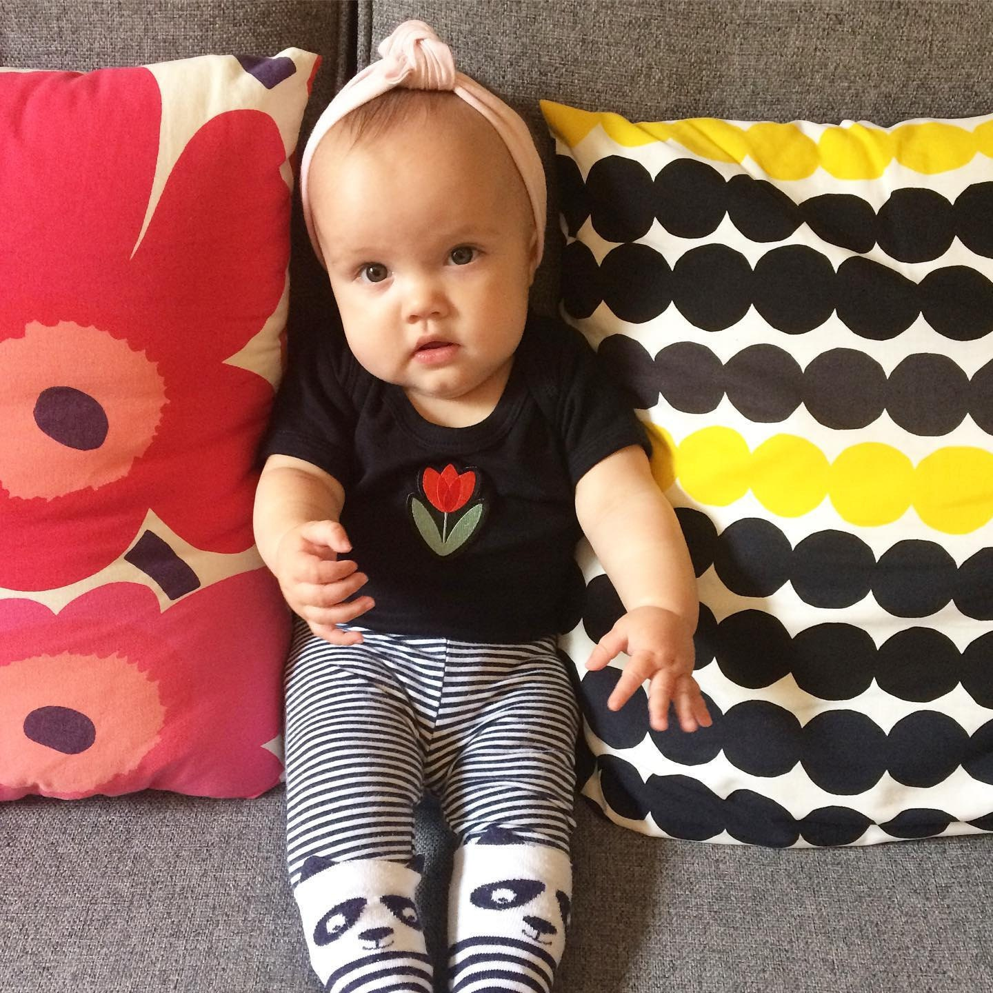 Lottie Piia wearing babygrow with Suzie London Tulip Embroidered patch